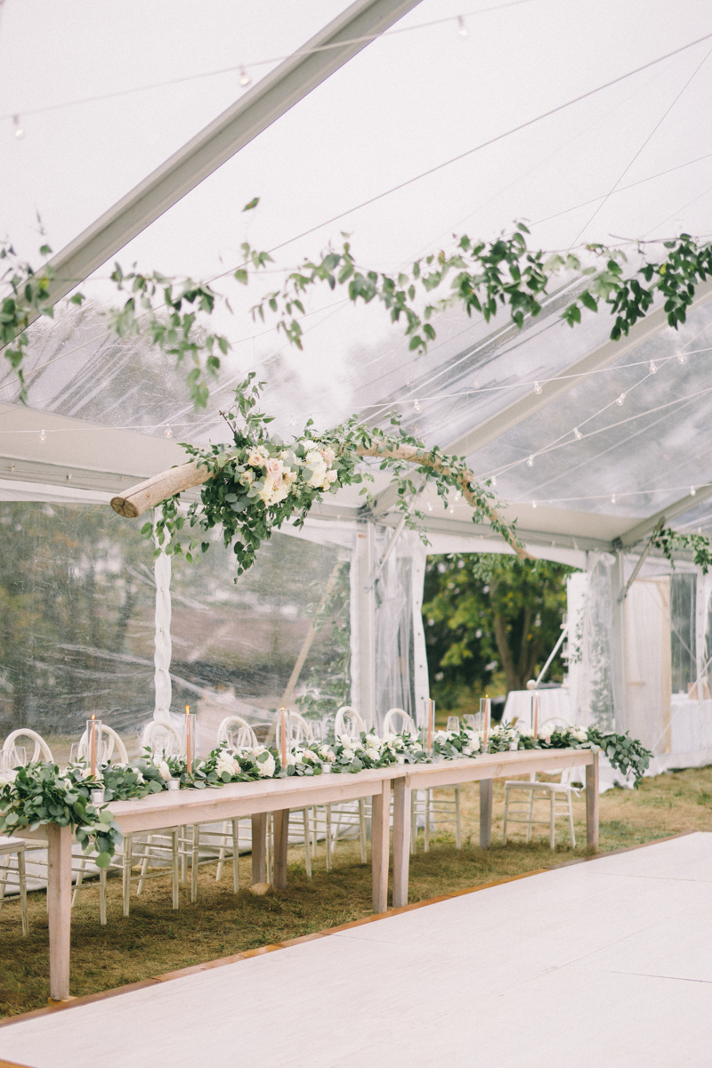 clear tent wedding with drift wood accents